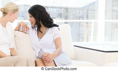 Smiling business women having fun sitting on sofa