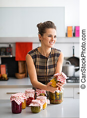 Smiling woman holding jar of preserved vegetables in kitchen...
