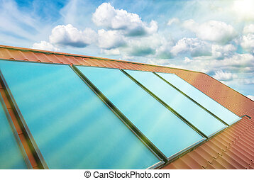 Solar cells on the red house roof under shining sun, blue...
