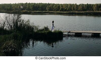 beautiful brunette in a white dress walks on the bridge