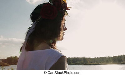 beautiful brunette with a wreath on her head looks into the distance