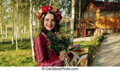 beautiful brunette with a wreath on his head and a bouquet of flowers in her hands looking at the camera and smiling