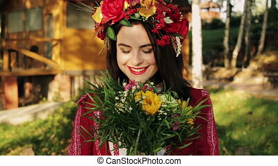 Beautiful Russian girl with a bouquet of flowers looking into the camera. Close-up