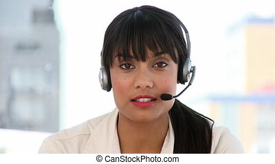 Attractive businesswoman talking on headset at work