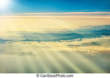 View from a plane to sunset on the sky with sunrays....