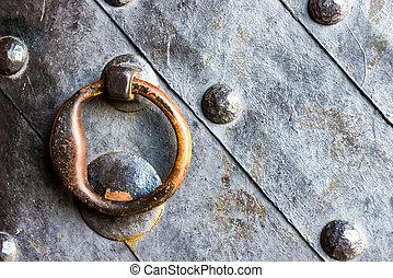 Old black door with ring knocker - Old black metal door in...