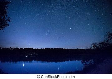 Beautiful night sky with many stars on a lake - Beautiful...