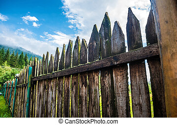 Old country fence with forest and blue sky on background
