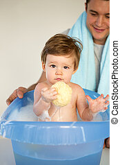 Baby's Bathtime - Father bathing his messy son in the bath....