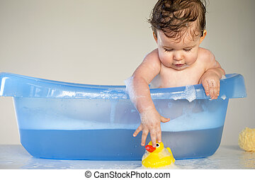 Playful Bathtime - Baby boy leaning over the side of his...