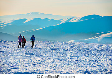People walking at sunset in winter mountains
