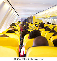 Aisle inside a plane. Interior with passengers on the seats