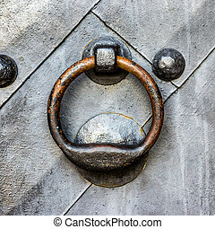 Old black door with ring knocker - Old black metal door in...