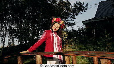 Beautiful girl in Russian national dress with a wreath on his head poses for the camera