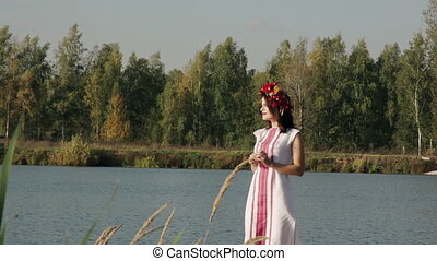 Beautiful girl in Russian national dress with a wreath on his head standing on the bridge near the lake