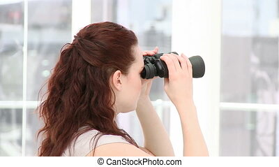 A woman looking through binoculars - Serious businesswoman...