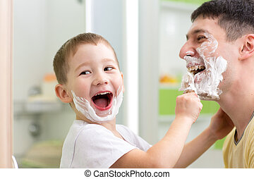 playful father and kid son shaving and having fun in...