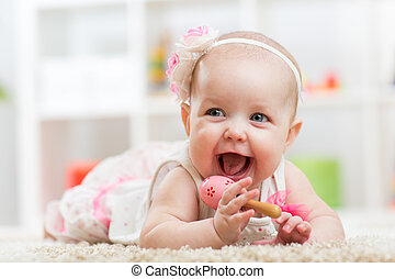 Smiling beautiful child girl lies with toy on carpet in...