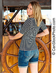 Young pretty woman with wooden ship's wheel.