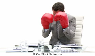 Competitive business man holding boxing gloves in his office...