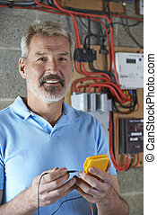 Portrait Of Electrician Standing Next To Fuseboard