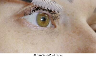 Woman Using Mascara On Her Eyelashe