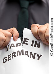 businessman tears a paper with the words, made in germany,...