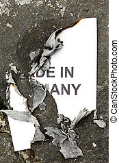 burned paper made in germany, lies on the ground, concept...