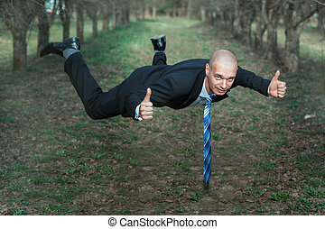 Man in a suit flying the park - Man in a suit flying in the...