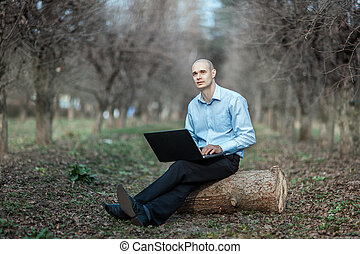 Man with dreaming face working at a laptop park - Man with a...