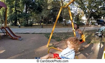 SLOW MOTION.  Children ride on the swings