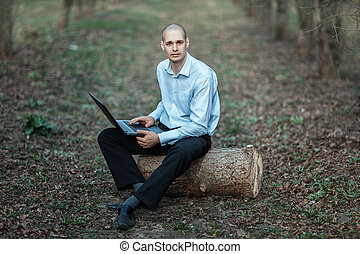 Successful intelligent man working at a laptop in the park...