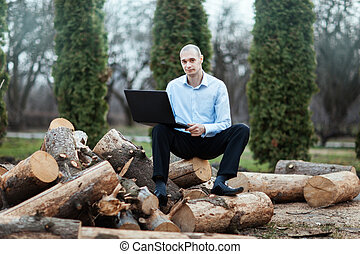 Man sitting log and working on a laptop - Man sitting on a...