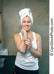 Smiling woman holding glass of water in bath