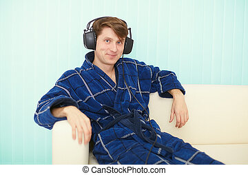 Man in big ear-phones sits on sofa