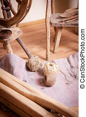 Distaff and skeins of thread on the floor beside it
