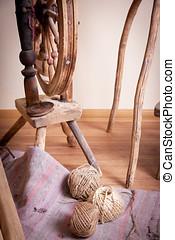 Three skein of thread on the floor near the distaff