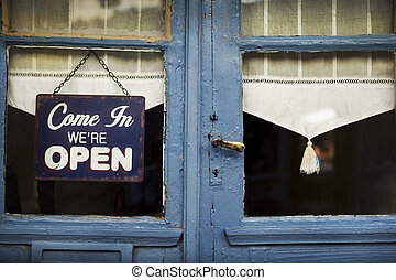 Open sign on the door of an old French bistro