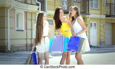 Three young cute girls discuss new purchases on a sunny afternoon