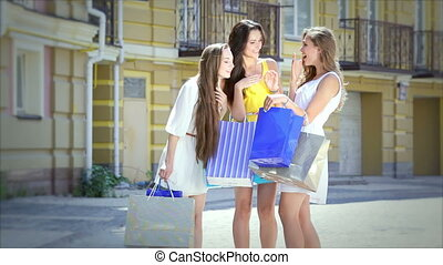 Three girls looking at shopping and then start to go merrily waving package