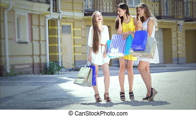 Shopaholic girls looking at shopping and then start to go merrily waving package