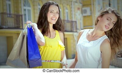 Two girls pleasing cuddling holding shopping bags