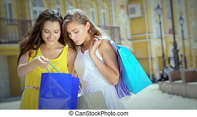 Young beautiful girlfriend emotionally look into shopping bags after shopping