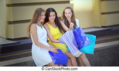Three cute girls sitting to discuss th selected fashion items from the boutique