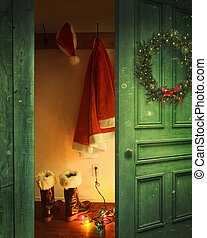 Open rustic door with Santa outfit hanging on hooks
