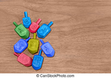 Group of colorful plastic Chanukah dreidels on worn wood...