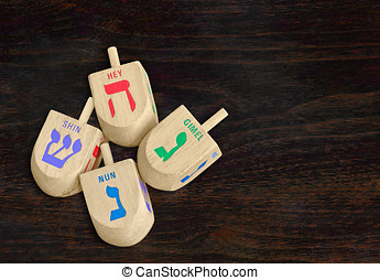 Group of Chanukah wooden dreidels on dark wood grain texture...