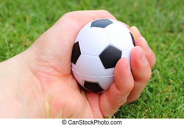Small stress ball in hand on grass background