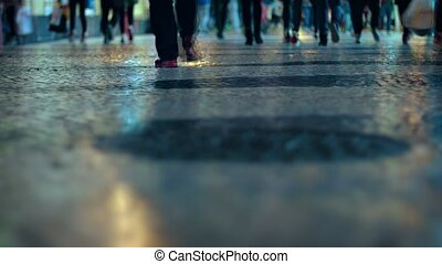 Shot, taken from a low angle, shows a crowd of strolling pedestrians