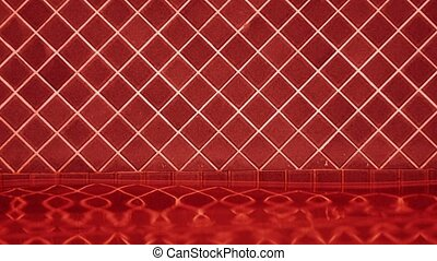Red tiles and white grout as the water sloshes back and...